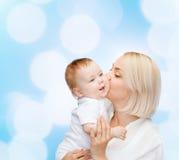 Kyssande behandla som ett barn le för lycklig moder Arkivfoto