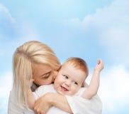 Kyssande behandla som ett barn le för lycklig moder Arkivfoton