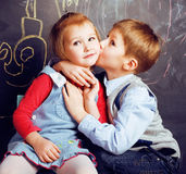 Kyssande blond flicka för liten gullig pojke i klassrum på svart tavla, första skolaförälskelse, livsstilfolkbegrepp Royaltyfri Foto