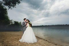 Kyssande brud för brudgum på flodbanken Royaltyfria Bilder