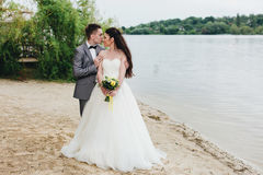 Kyssande brud för brudgum på flodbanken Arkivfoton