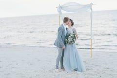 Kyssande brud för brudgum på kusten Arkivbild