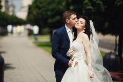Kyssande brud för brudgum på stadsgränden suddighet bakgrund Arkivfoto