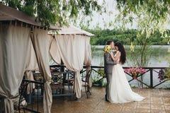 Kyssande brud för brudgum på verandan Arkivbilder