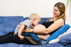 Kyssande buk för pys av den gravida modern på soffan Royaltyfria Bilder