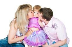 kyssande föräldrar för dotter Arkivbild