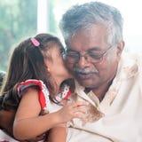 Kyssande farfar för sondotter Arkivbild