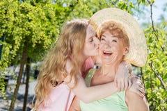 Kyssande farmor för sondotter i en sommarträdgård Royaltyfri Fotografi