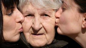 Kyssande farmor för ung flicka och för vuxen kvinna på kinder, farmor som ler och ser till kameran familj tre Royaltyfri Bild