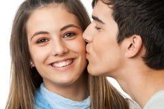 Kyssande flickvän för pojkvän på kind. Royaltyfri Fotografi