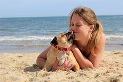 Kyssande ägare för mopshund på stranden Arkivfoton