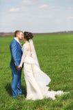 Kyssande gift par på grönt fält Royaltyfria Foton