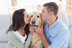 Kyssande golden retriever för par på soffan Royaltyfri Bild