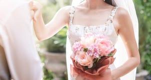 Kyssande hand för brudgum av hans älskvärda brud Gifta sig som är utomhus- royaltyfri bild