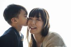 Kyssande kind för son hans mamma med förälskelse fotografering för bildbyråer