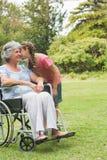 Kyssande kind för sondotter av farmodern i rullstol Royaltyfria Bilder