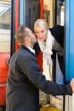 Kyssande kvinna för man goodbye på kinddrevet Royaltyfri Foto
