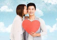 Kyssande man för kvinna som rymmer en hjärta Fotografering för Bildbyråer