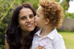 Kyssande moder för pojke på henne kind royaltyfri foto