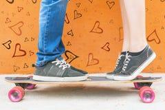 Kyssande par för Closeup på skateboarden och röd väggbakgrund Royaltyfria Bilder