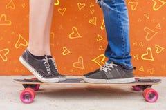 Kyssande par för Closeup på skateboarden och röd väggbakgrund Royaltyfri Foto