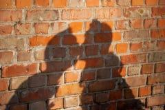 Kyssande par för skugga på en tegelstenvägg Royaltyfri Bild