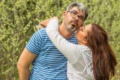 Kyssande par framme av skogen Arkivfoto