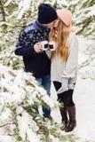 Kyssande par med varma drinkar i skog bland granträd Arkivbild