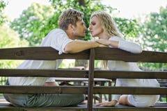 Kyssande par på bänken Royaltyfri Foto