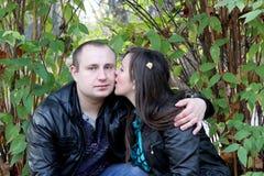Kyssande pojke för flicka på kinden arkivbild