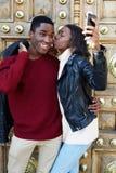 Kyssande pojkvän för kvinna på kinden som fotograferar sig med smartphonen Royaltyfri Foto