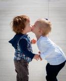 Kyssande små barn, sidosikt som står Arkivfoton
