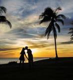 kyssande solnedgång för par Arkivbilder