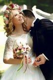 Kyssande stilig brudgum för härlig lycklig ung brud i solbelyst medeltal Arkivbilder