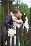 Kyssbrud och brudgum om trästaket Royaltyfri Bild