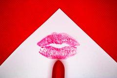 Kyssfläck och den röda läppstiftet på vitboken med den röda bakgrunden - bild royaltyfri fotografi