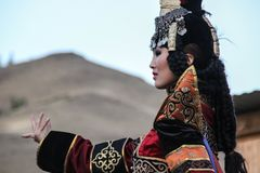 Mongolian woman in shaman and witch costume dances on stage in the mountains. Tyva folk dances stock images