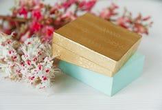 Là l'or et les boîtes bleues avec les branches blanches et roses de l'arbre de châtaigne sont sur le Tableau blanc, foyer sélecti Photo libre de droits
