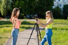 Là où petit les adolescentes pendant l'été en parc enregistrent la vidéo sur l'appareil-photo Gesticule avec émotion avec le sien images libres de droits