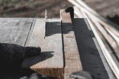 Lámina de sierra el coche asierra la madera hay una pizarra en el fondo Mano de trabajo foto de archivo libre de regalías