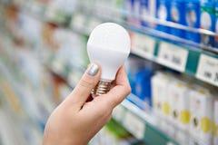 Lámpara ahorro de energía del LED en manos del comprador en la tienda Imagen de archivo