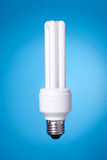 Lámpara ahorro de energía en fondo azul Imagenes de archivo