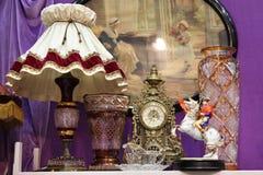 L?mpara antigua con pantalla, el reloj y los floreros de cristal grandes imagen de archivo