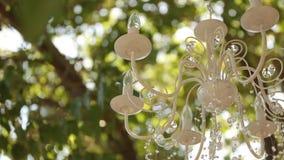 Lámpara cristalina con las flores y las guirnaldas en ceremonia de boda Decoración del día de fiesta, estilo rústico metrajes