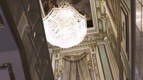 Lámpara cristalina de Beautifuul que cuelga del techo adornado dentro del palacio, arte, concepto histórico de las decoraciones almacen de metraje de vídeo