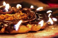 Lámpara de aceite de Diwali con las llamas y los pétalos secados de la flor foto de archivo libre de regalías