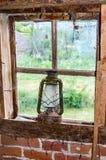 Lámpara de aceite en ventana rota vieja Fotografía de archivo libre de regalías