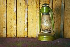 Lámpara de aceite vieja en un fondo de madera amarillo Fotos de archivo libres de regalías