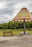 Lámpara de cabecera gigante y un banco en un parque público debajo de un cielo cubierto del verano imagen de archivo libre de regalías