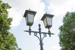 Lámpara de calle antigua en el fondo de las nubes de los árboles del cielo azul fotos de archivo libres de regalías